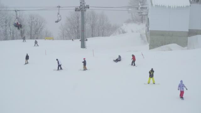 skiers and snowboarders at gala yuzawa ski resort, niigata, japan - スキー板点の映像素材/bロール
