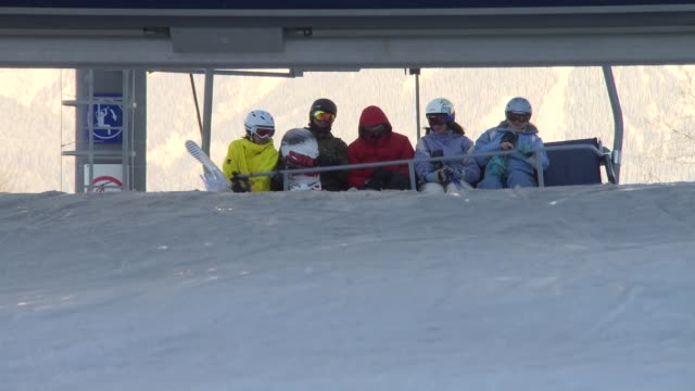 vídeos y material grabado en eventos de stock de skiers and snowboarders disembarking skilift at mountaintop / wide shots skiers descending mountain slope / low angle view male skier skiing over... - sochi