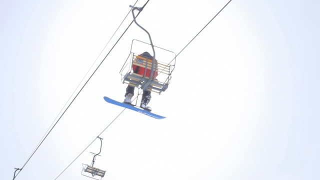 Skiers and snowboarders ride a ski lift at Snowbird, Utah.