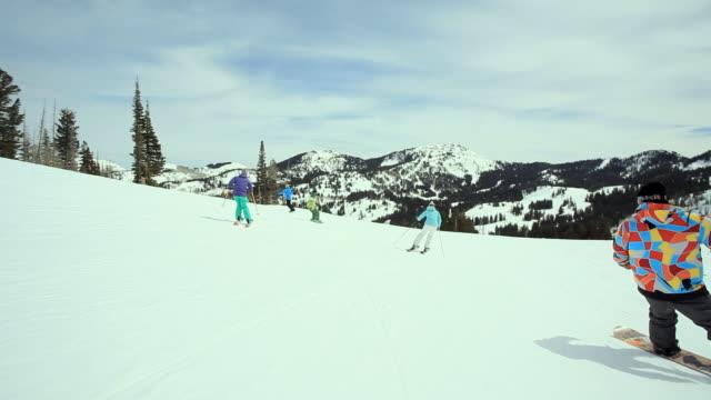 vídeos y material grabado en eventos de stock de ws pov skiers and snowboarders riding down slope at ski resort / brighton ski resort, utah, usa - chaqueta de esquiar