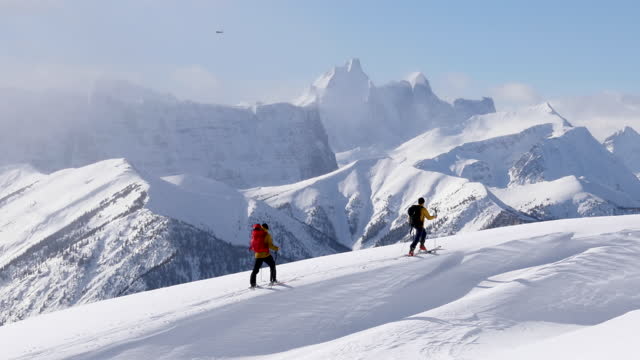 skiers ascend to high mountain peak with snowy mountains behind - snowcapped mountain stock videos & royalty-free footage