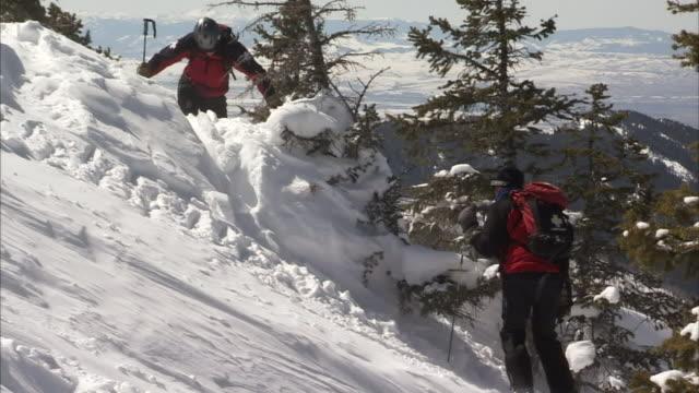 skiers climb up a snowy hill. - 踏む点の映像素材/bロール