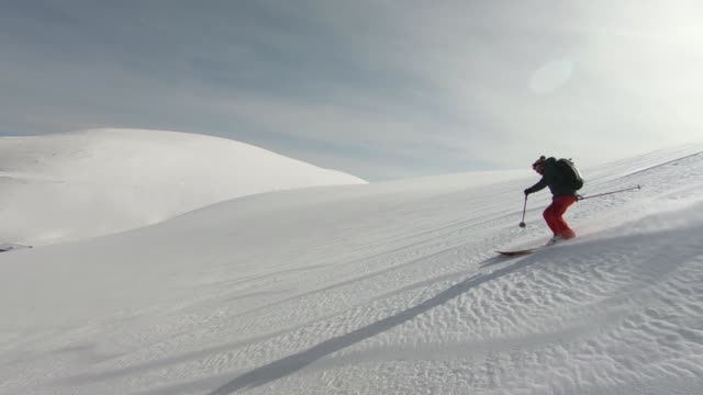 Skiers descending mountain in deep snow powder