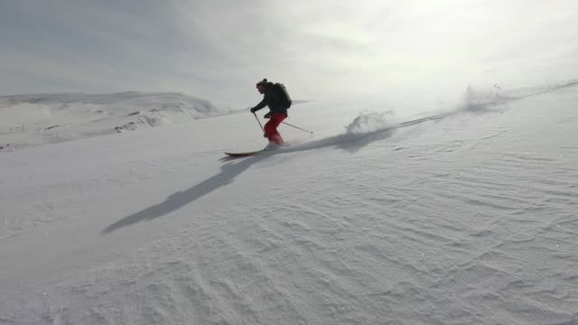 skiers descending mountain in deep snow powder - ski jacket stock videos and b-roll footage