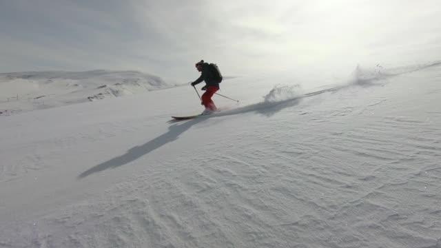 Skiers descending mountain in deep snow powder