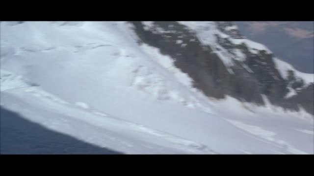 WS POV Skiers forward on steep mountain slope through crevasse and traverses steep hill