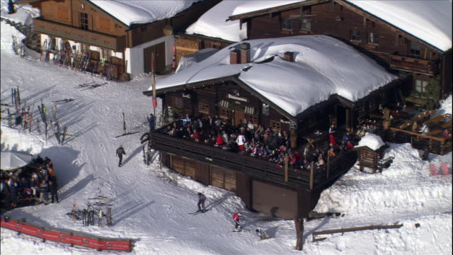 skiers gather in an outdoor cafe at a mountaintop ski lodge in austria. - ski lodge stock videos & royalty-free footage