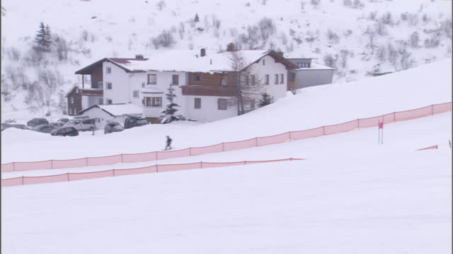 skiers glide down snowy slopes past a ski lodge. - ski lodge stock videos & royalty-free footage