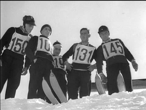 / skiers lined up prior to jump making 'heil hitler' salute / ski jumper birger ruud of norway winner of ski jump competition / ruud soaring through... - garmisch partenkirchen stock videos & royalty-free footage