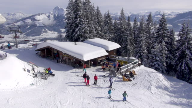 Skiers move past a Tyrolean mountain cafe.