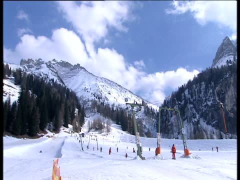 skiers on ski lifts going up ski slope with huge snow covered mountains in background - traditionally austrian stock videos & royalty-free footage