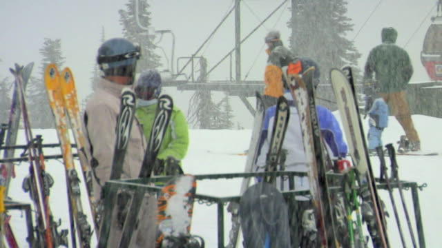 MS, Skiers placing skis on ski rack, ski lift in background, Whitefish, Montana, USA