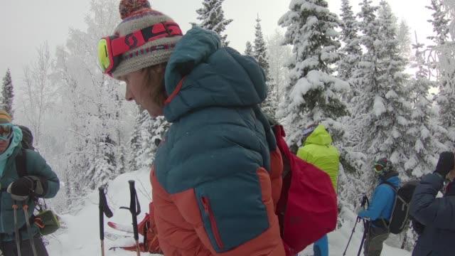 skiers prepare to descend mountain - ski jacket stock videos & royalty-free footage