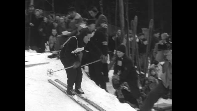 skiers push themselves off at starting line while spectators stand by / skiers zoom down slalom course / note exact day not known - 1952 bildbanksvideor och videomaterial från bakom kulisserna