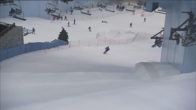 skiers race down slopes in ski dubai. - ski lift stock videos & royalty-free footage