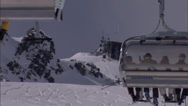 skiers ride a lift above snowy slopes. - ski lift stock videos & royalty-free footage