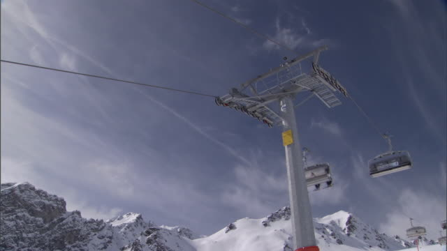 skiers ride a lift in the alps. - seggiovia video stock e b–roll