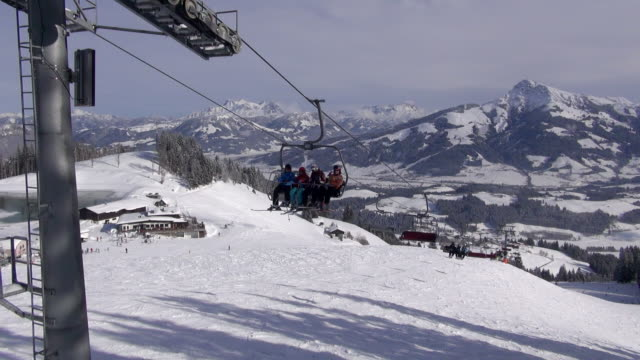 Skiers ride a lift up an Alpine mountainside.