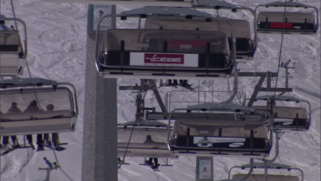 skiers ride chair lifts up and down snowy mountains in switzerland. - switzerland stock videos & royalty-free footage