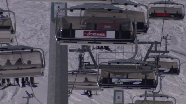 skiers ride chair lifts up and down snowy mountains in switzerland. - ski resort stock videos & royalty-free footage