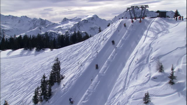 skiers ride up a ski hill on a t-bar in austria. - stazione sciistica video stock e b–roll