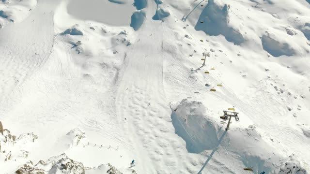 skiers rushing down the ski slope on a beautiful sunny day - ski flying stock videos and b-roll footage