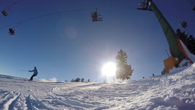 stockvideo's en b-roll-footage met 4k skiërs skiën en rijden ski lift op zonnige, besneeuwde skipiste, real-time - skigebied