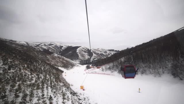 skiers skiing at winter ski resort chongli, zhangjiakou, china - inquadratura dalla sciovia video stock e b–roll