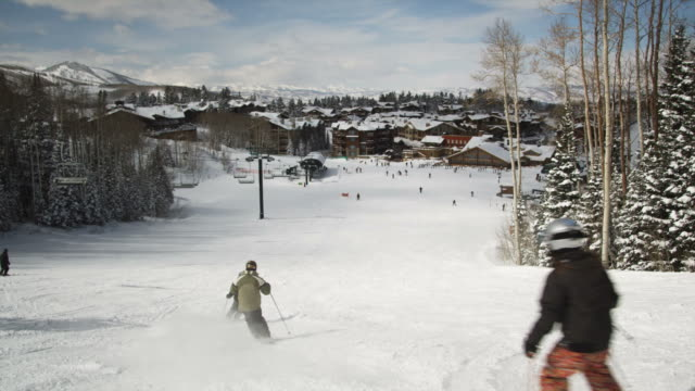 skiers skiing down the slopes at a ski resort - utah stock-videos und b-roll-filmmaterial
