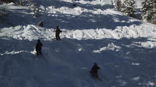 vídeos de stock, filmes e b-roll de skiers skiing down the slopes at a ski resort - três pessoas