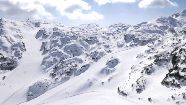 aerial skiers skiing down the slopes on sunny day - european alps stock videos & royalty-free footage