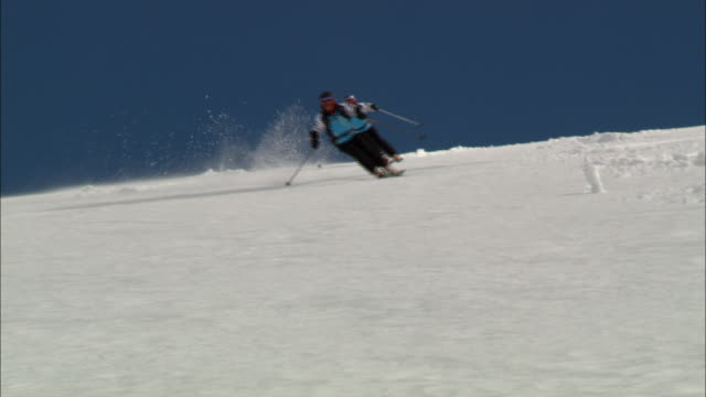 skiers traverse down a snowy mountainside. - winter sport stock videos & royalty-free footage