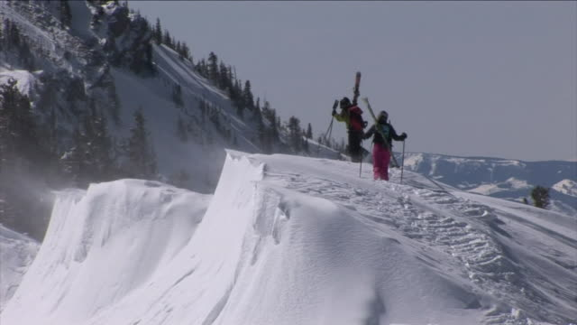 vidéos et rushes de skiers traverse snow drifts on a mountain top. - neige fraîche
