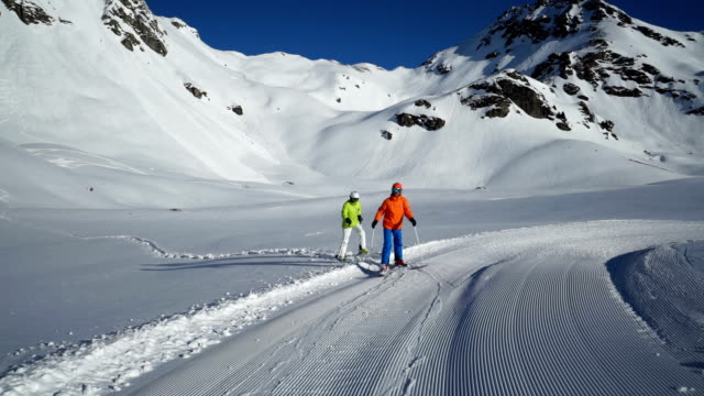 skiers walking back to ski piste giving high five - ski jacket stock videos and b-roll footage