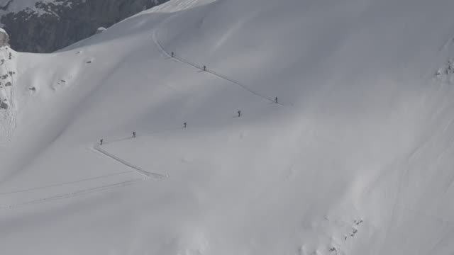 skiers walking in the snow to a mountain top - ジグザグ点の映像素材/bロール