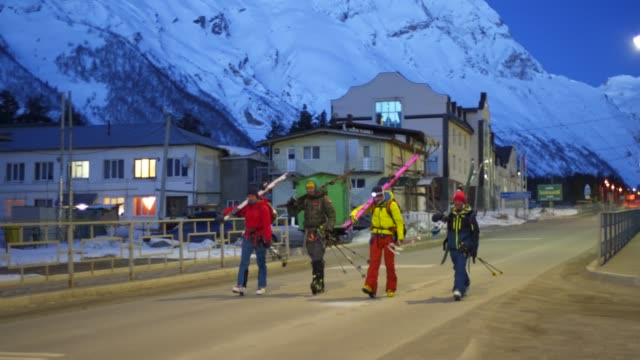skiers walking towards the camera at dawn through a small town - four people stock videos & royalty-free footage