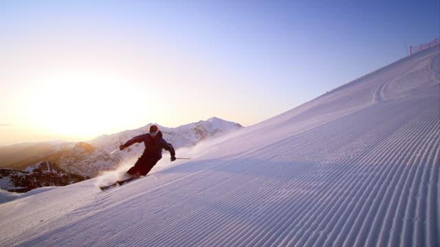 vídeos de stock e filmes b-roll de slo mo skiing down a freshly groomed track at sunrise - bastão de esqui