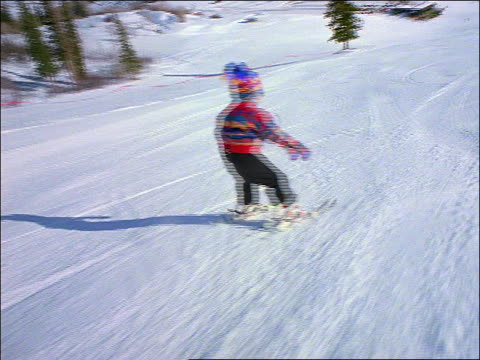 Skiing point of view behind child skiing down slope w/out poles