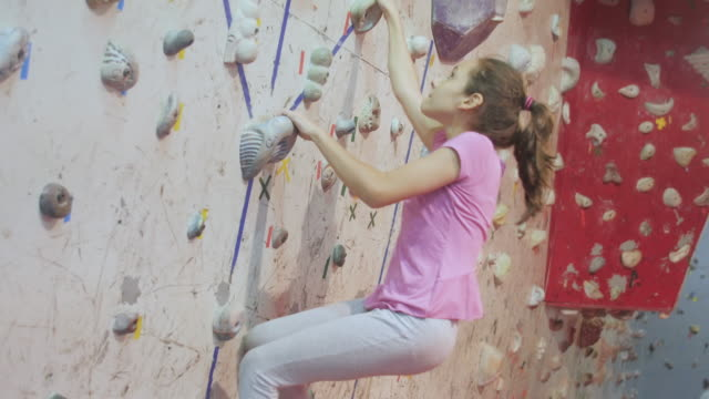 skilled 12 year old girl free climbing at an indoor climbing site - free climbing stock videos & royalty-free footage
