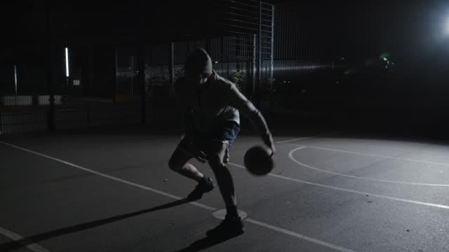 vídeos de stock e filmes b-roll de skilled athlete dribbling basketball at night - saltar para cima e para baixo