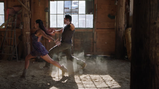 slo mo. skilled ballroom dancers perform synchronized routine by sunlit window in rustic barn. - fishnet stock videos and b-roll footage