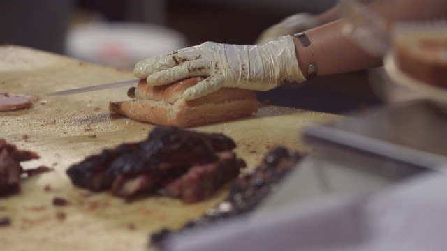 Skilled barbecue cook slices bread in restaurant kitchen