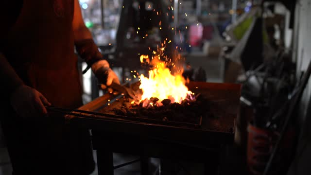 a skilled blacksmith works in his workshop while fanning his fire to reach a higher temperature. - steel stock videos & royalty-free footage
