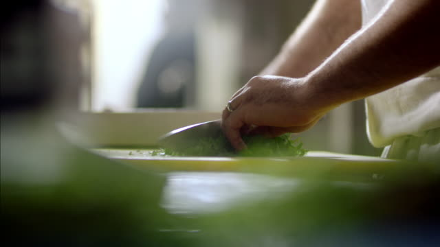 Skilled chef mince cuts parsley in restaurant kitchen