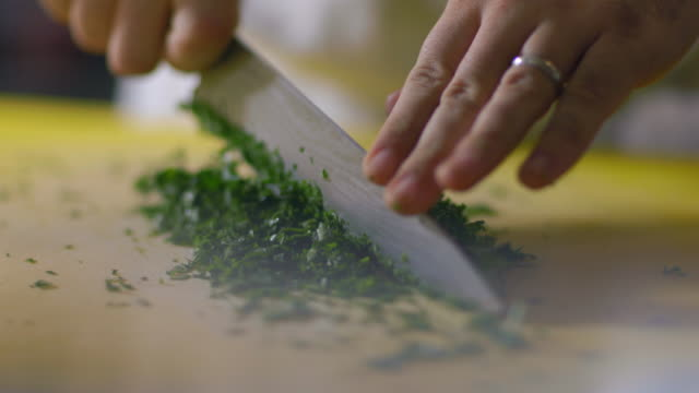 Skilled chef mince cuts parsley on kitchen table in restaurant