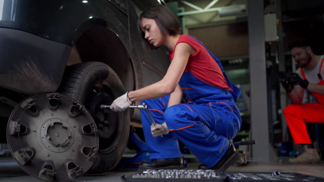 skilled female mechanic working at a car shop - medical glove stock videos & royalty-free footage