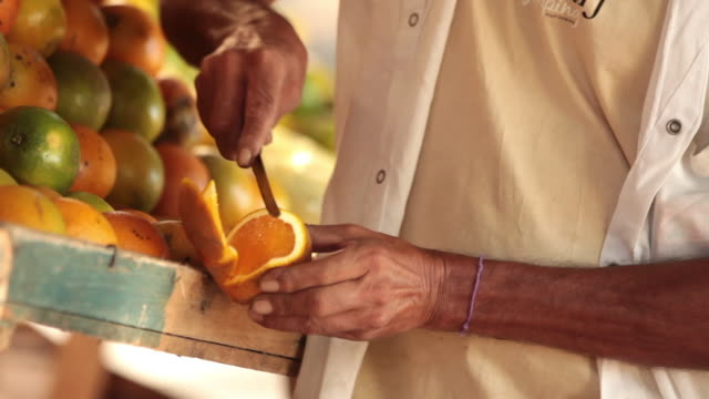 vidéos et rushes de skilled hands slice orange with knife in brazilian market - acide ascorbique