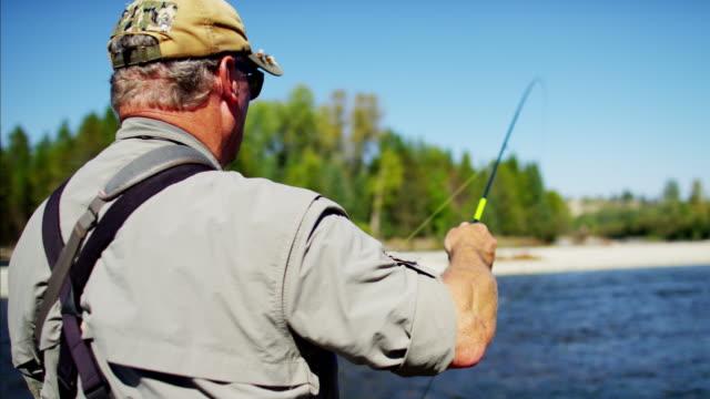 vidéos et rushes de skilled hobby fisherman casting line freshwater fishing canada - lancer la ligne de canne à pêche