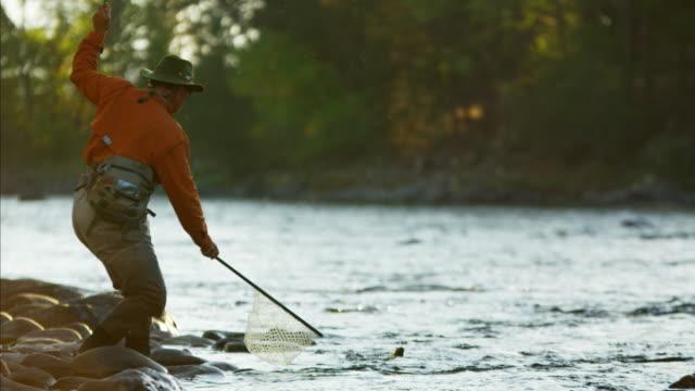 stockvideo's en b-roll-footage met skilled hobby fisherman casting line freshwater fishing canada - hengel uitwerpen