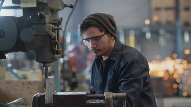 stockvideo's en b-roll-footage met slo mo skilled industrial worker turns on and manually operates lathe machine in warehouse - metaalindustrie